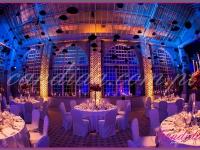 dekoracja sali jadalnej, na stołach kandelabry z kompozycjami kwiatowymi i świecami, pod sufitem podwieszone meloniki, dekoracje eventowe, kwiaty dla firm