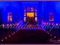 wejście utworzone przez szpaler pochodni i świec, w tle widać drzewo z balonów, dekoracje eventowe, kwiaty dla firm