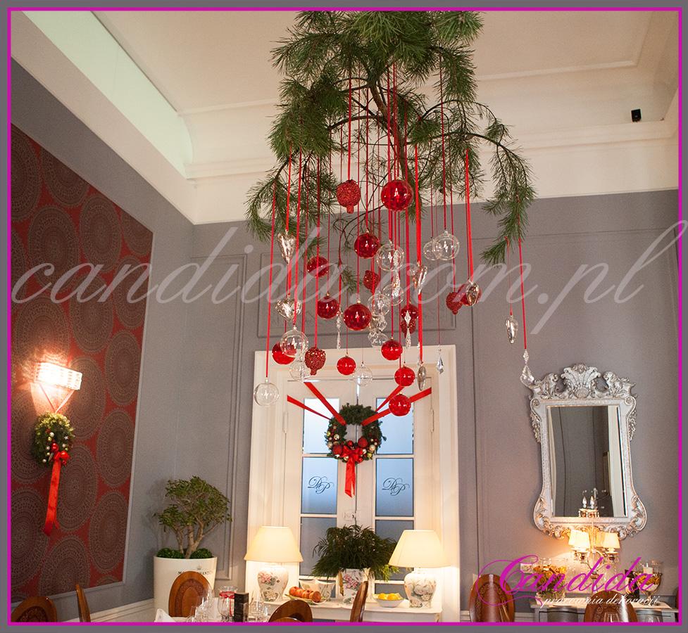 gałąź sosny z ozdobami świątecznymi podwieszona pod sufitem